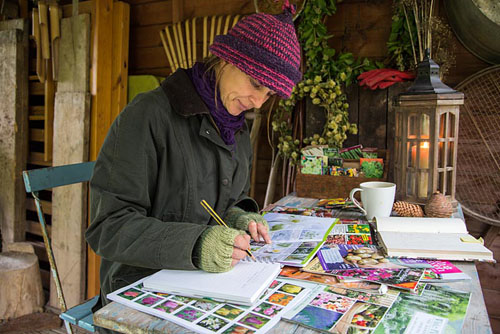 Woman sat in shed garden planning during Winter, for the following year to come - © GAP Photos
