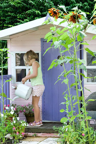 Young girl watering containers with watering can outside of painted wendy house - © Juliette Wade/GAP Photos