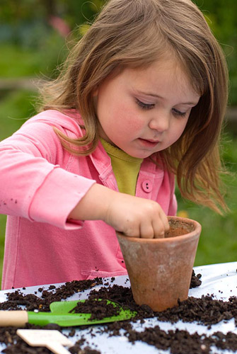 Little girl planting sunflower seeds - © Richard Bloom/GAP Photos