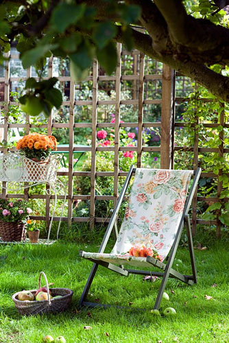 Deckchair on lawn and a bunch of orange Dahlias - © Juliette Wade/GAP Photos