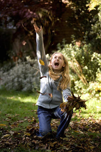 Girl playing with fallen leaves - © Paul Debois/GAP Photos