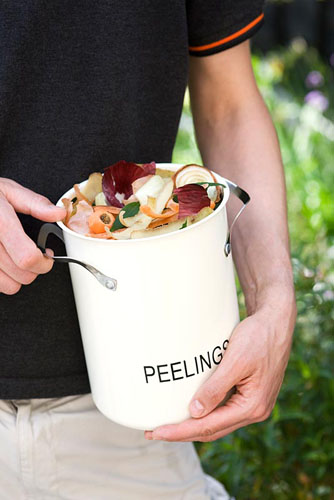Taking container of collected green kitchen waste to the compost bin in the garden - © Victoria Firmston/GAP Photos