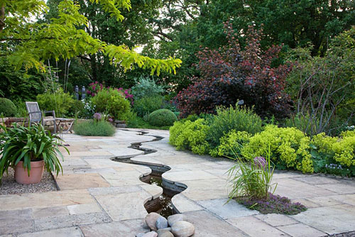 A meandering canal through flagstone paving, background of shrubs, old trees and a dry stone wall - © Christa Brand/GAP Photos