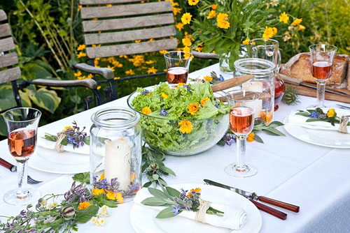 Table set for meal with wooden chairs, decoration with Calendula officinalis and Borago officinalis - © Manuela Goehner/GAP Photos