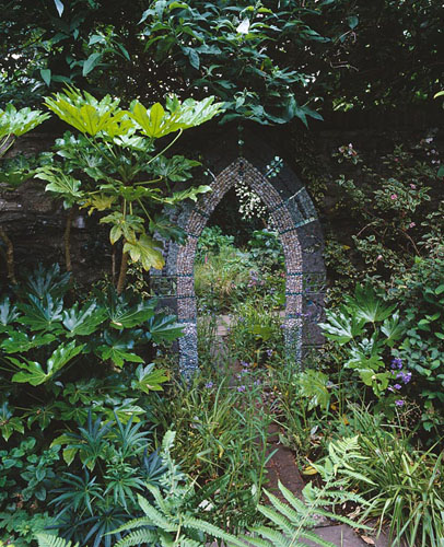 A mosaic mirror with shells, pebbles and tiles is surrounded by Hedera 'Goldheart', Polemonium caeruleum, Fatsia japonica and Ficus 'Brown Turkey' - © Clive Nichols/GAP Photos