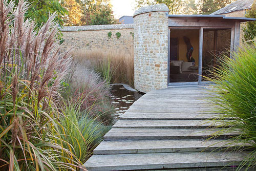 Mixed grasses in autumn including Miscanthus Malepartus and Gracillimus alongside wooden bridge to summerhouse - Farrs - © Abigail Rex/GAP Photos