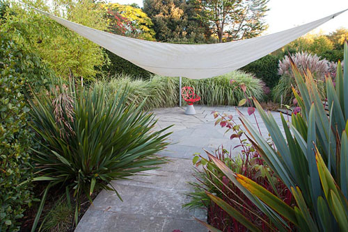 Contemporary red chair on circular patio with sail shade, Miscanthus and Phormium - Farrs - © Abigail Rex/GAP Photos