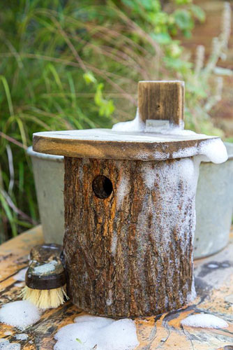 Cleaning a Birdhouse. Leave the birdhouse to air dry before hanging back in place - © GAP Photos