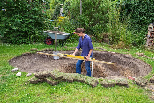 Step by step for creating a wildlife pond - ensuring ground is level - © GAP Photos