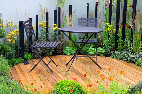 Small decked area with simple table and chairs in 'Spiral' garden - © Mark Bolton/GAP Photos