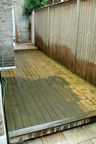 Area of decking down the side of a terraced town house in the process of being cleaned using a pressure washer - © Mel Watson/GAP Photos