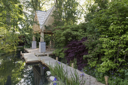 The M&G Garden, The Retreat - view toward oak summerhouse with wooden decking next to natural swimming pond pool acer hedging and irises next to water- designer Jo Thompson - sponsors, M &G Investments - awarded Silver Gilt - © Stephen Studd/GAP Photos