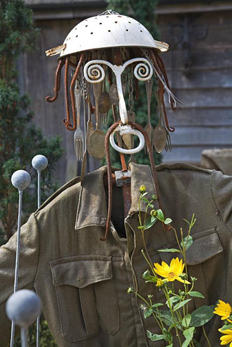 Seaside Inspired garden. Scarecrow made from old pitchfork, colander, old cutlery with army jacket.