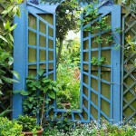 Garden mirror feature with blue painted surround with 'Green man' themed painting at top