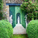 Trompe l'oeil - mural next to Buxus sempervirens and Honeysuckle - The West Garden, Daglingworth House, Gloucestershire, UK. June