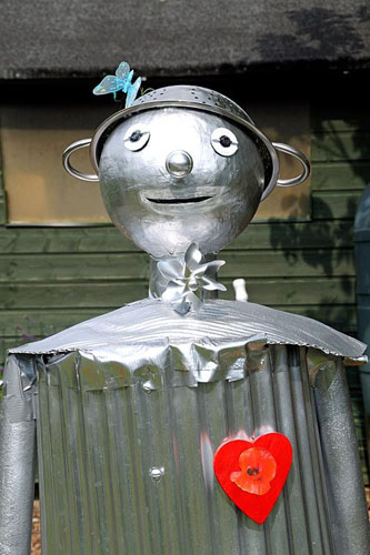 The Tin Man Scarecrow from The Wizard of Oz with colanders for hat and a red heart, Paddock Allotments