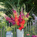 Outdoor display with Gladiolus, Foeniculum and grasses in metal vase