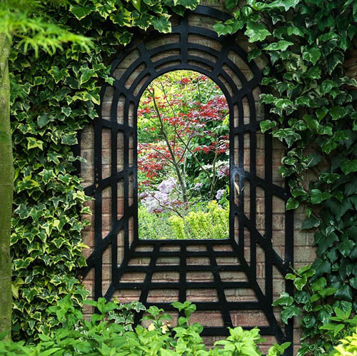 A mirror trompe l'oeil creates a focal point on a garden wall. Made from mirror from local hardware store, the surround from reclaimed batoning.