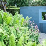 Ammonite sculpture by Darren Yeadon framed by a window in a grey wall trompe l'oeil - on one side of the flower garden, with lush ferns and pink astrantias in the foreground. Tony Ridler's garden, Swansea, Wales, UK
