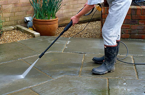 Using pressure washer to clean patio slabs - © Michael Howes/GAP Photos