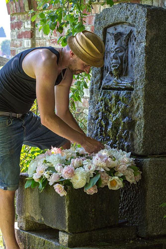 Flower artist arranging peony wreath in a granite trough under a waterspout. Varieties are 'Jan van Leuwen', 'Sarah Bernhard' and 'Mme. Claude Tain' - © Christa Brand/GAP Photos