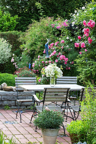 Wood and iron garden furniture on a brick stone terrace in a pottery maker's garden with ceramic objects and Rosa 'Leonardo da Vinci', 'New Dawn' and 'Rosarium Uetersen'