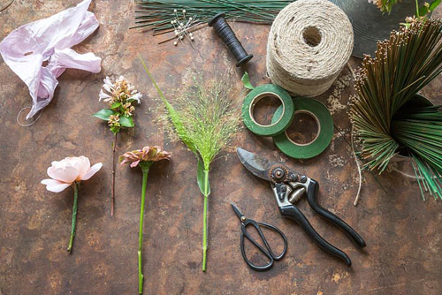 Ingredients required for making a Wedding Buttonhole. Featuring Zinnia elegans 'Queen Red Lime', Rosa 'Ambridge Rose', Panicum elegans 'Frosted Explosion' and Abelia x grandiflora - © GAP Photos