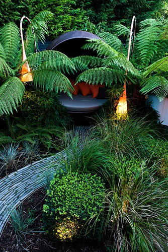 Modern lighting and covered seating area surrounded by Dicksonia antarctica and Polystichum setiferum ferns - © John Glover/GAP Photos
