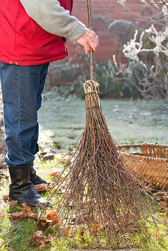 Making a Birch broom - man tidying leaves from the lawn using newly made birch broom - © Robert Mabic/GAP Photos