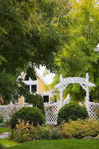 White wooden arbour with trellis fence in front garden in autumn. Plantings include globe shaped cedar 'Thuja occidentalis' trees and an artist's workshop. Il Etait Une Fois garden, Monteregie, Quebec, Canada - © Perry Mastrovito/GAP Photos