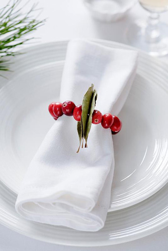 Making a Cranberry and Bay leaf decorative ring - using the decoration as a napkin ring - © Victoria Firmston/GAP Photos