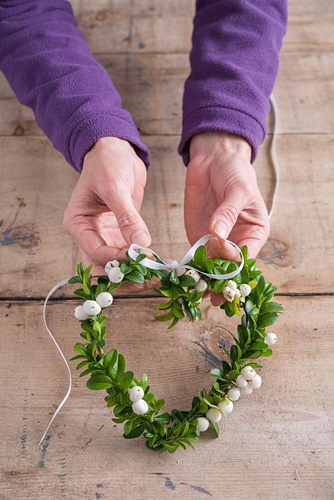Tying decorative ribbon on snowberry and buxus heart shaped wreath to hang - © GAP Photos