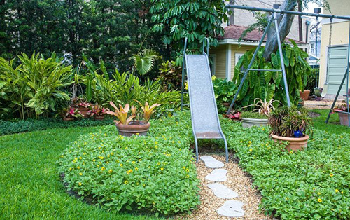 Childrens play equipment in garden with mature planting of Helianthus debilis, Neoregelia, Codiaeum, Alpinia and Philodendron - © Jerry Pavia/GAP Photos
