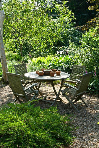 Wooden table and chairs in front woodland garden, June. Sandhill Farm House, Hampshire - © Jo Whitworth/GAP Photos