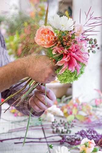 Beginning the construction of the vibrant bouquet with Crataegus monogyna, Dahlia 'Labyrinth', Rosa 'Ambridge Rose', Rosebay willowherb seed pods and Hydrangea arborescens 'Annabelle' - © GAP Photos