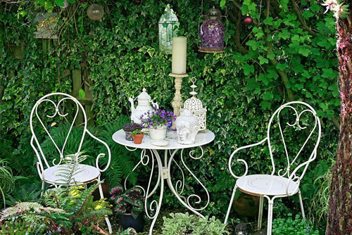 White wirework chairs and table and carefully chosen ornaments make a striking focal point in a shady, private seating area of a town garden - © Graham Strong/GAP Photos