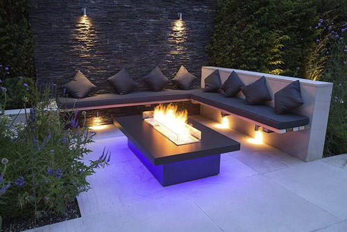 Secluded seating area with a dry stone slate wall and propane fire pit emitting blue light -  © GAP Photos