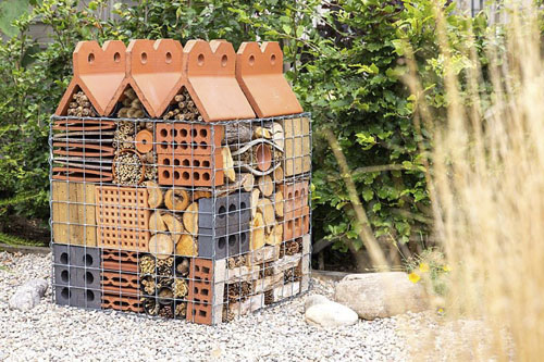 Insect hotel created in wire gabion with a variety of building materials and dried plant material - © GAP Photos