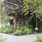 The RHS Back to Nature Garden  – tree house made from wood and tree branches, wooden ladder made from tree slab, rope swing, wooden decking board walk, planting of ferns and shade loving plants - Designer: HRH The Duchess of Cambridge with Andree Davies and Adam White - Sponsor: The RHS