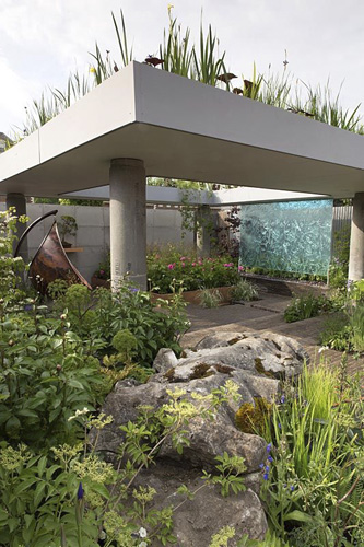 The Silent Pool Gin Garden, view of sunken garden with glass wall water feature, corrugated metal fencing, recycled concrete pillars supporting a roof with water garden, old limestone boulders,  clay brick wall and paving,  copper swing chair, roses, grasses – Designer: David Neale - Sponsor: Silent Pool Gin - ©  GAP Photos/Stephen Studd