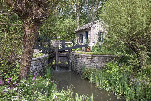Canal lock and lock keeper's cottage with native flora including red campion and willow, The Welcome to Yorkshire Garden, Design: Mark Gregory, Sponsor: Welcome to Yorkshire, Gold Medal Winner - © GAP Photos/Andrea Jones
