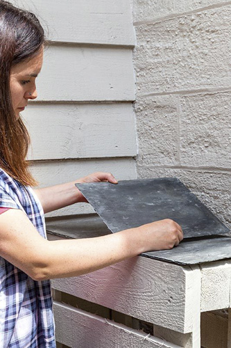 Placing cut slate tiles on pallets to create working surface