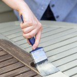 Woman painting garden furniture with paint brush
