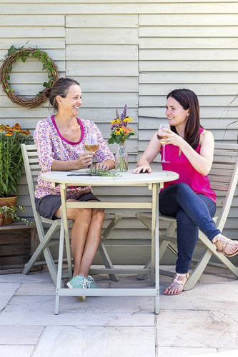 Women sat at wooden painted garden table