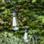 A string of retro-style outdoor lights suspended in a garden.