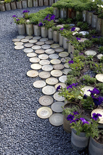 Hundreds of tin cans stacked and built to edge borders. All filled with plants and herbs. Tin bottoms and black pebbles combined as a decorated surface - © GAP Photos/Hanneke Reijbroek