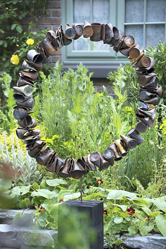 The Great Chelsea Garden Challenge. Circular sculpture made from rusted old steel cans - © GAP Photos/Andrea Jones