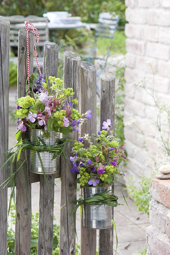 Aquilegia, Geranium, Alchemilla and Nepeta displayed in tin cans - © GAP Photos/Friedrich Strauss