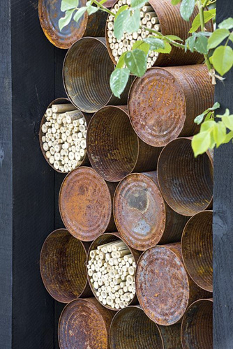 The Great Chelsea Garden Challenge Garden. Rusted alluminium cans used for insect hotels. Designer - Sean Murray. Sponsor - Royal Horticultural Society - © GAP Photos