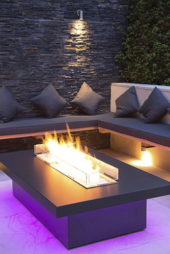 Secluded seating area with a dry stone slate wall and propane fire pit emitting purple light - © GAP Photos